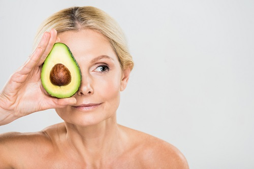 After a shower, a beautiful woman holds an avocado half up to her face denoting ways to combat chronic stress and skin problems
