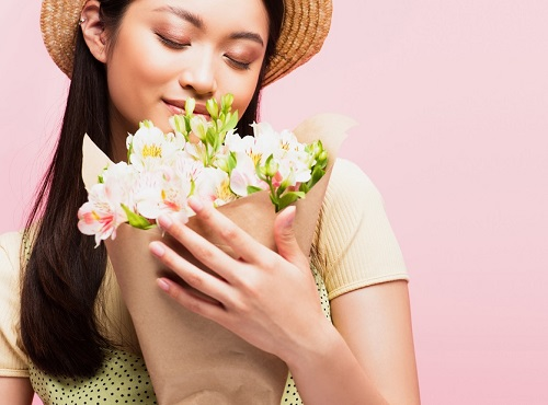 Can scent affect your mood? Definitely! This woman is calmed and happy after smelling flowers.